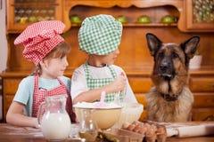 Dos pequeños cocineros que gozan en la cocina que hace lío grande alemán Imagen de archivo