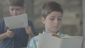 Dos pequeños hermanos de gemelos en el cuarto ahumado Un muchacho encendió el papel con un encendedor en el fondo mientras que ot metrajes