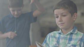 Dos pequeños hermanos de gemelos en el cuarto ahumado Un muchacho encendió el papel con un encendedor en el fondo mientras que ot almacen de metraje de vídeo