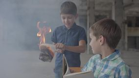 Dos pequeños hermanos de gemelos en el cuarto ahumado Un muchacho encendió el papel con un encendedor y otra lectura del niño en almacen de metraje de vídeo