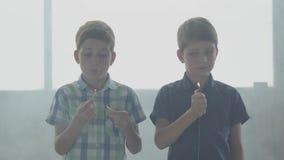 Dos pequeños hermanos de gemelos que juegan con el fuego en el cuarto ahumado delante de una ventana Niños que ponen hacia fuera  almacen de video