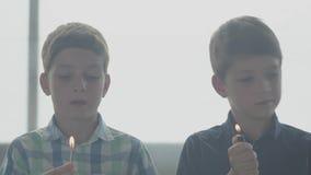 Dos pequeños hermanos de gemelos que juegan con el fuego en el cuarto ahumado delante de una ventana Niños que ponen hacia fuera  metrajes
