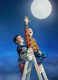 Dos pequeños hermanos que cogen la luna Imagen de archivo libre de regalías