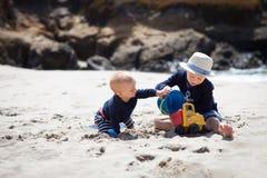 Dos pequeños hermanos que juegan el togther en la playa Fotos de archivo