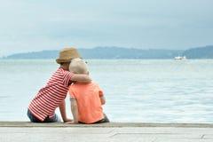 Dos pequeños hermanos se sientan en un embarcadero y abrazan contra el mar y las montañas en la distancia Visión posterior Fotografía de archivo