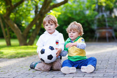 Dos pequeños muchachos de la fan en la visión pública del partido de fútbol Imagen de archivo libre de regalías