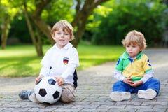 Dos pequeños muchachos de la fan en la visión pública del partido de fútbol Foto de archivo libre de regalías