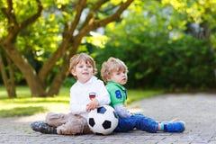 Dos pequeños muchachos de la fan en la visión pública del partido de fútbol Imagenes de archivo