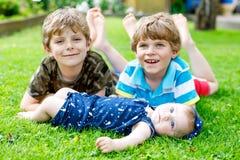 Dos pequeños muchachos felices del niño con el bebé recién nacido, hermana linda Imagenes de archivo