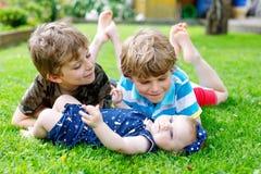 Dos pequeños muchachos felices del niño con el bebé recién nacido, hermana linda Foto de archivo libre de regalías