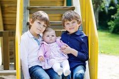 Dos pequeños muchachos felices del niño con el bebé recién nacido, hermana linda Imagen de archivo libre de regalías