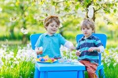 Dos pequeños muchachos gemelos en los oídos del conejito de pascua que colorean los huevos Fotografía de archivo libre de regalías