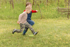 Dos pequeños muchachos que corren a través de un campo Fotografía de archivo