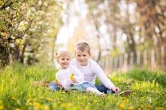 Dos pequeños niños caucásicos lindos, muchacho y muchacha, sentándose en una hierba Fotografía de archivo