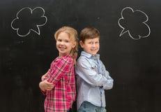 Dos pequeños niños con frase se nublan en la pizarra Foto de archivo