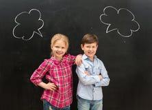 Dos pequeños niños con frase se nublan en la pizarra Fotos de archivo
