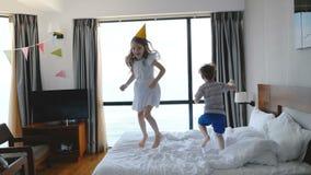 Dos pequeños niños de 5-8 años caucásicos felices, hermano y hermana, saltando alegre en cama en un cuarto ligero, divirtiéndose almacen de metraje de vídeo