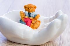 Dos pequeños niños del oso que juegan negligentemente mientras que está protegido en una mano blanca fotografía de archivo