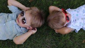 Dos pequeños niños en las gafas de sol que mienten en la hierba en parque Visión desde la tapa almacen de metraje de vídeo