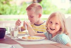 Dos pequeños niños felices que comen el desayuno sano en casa imagenes de archivo