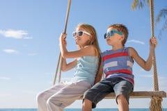 Dos pequeños niños felices que juegan en la playa en el tiempo del día Imágenes de archivo libres de regalías