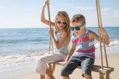 Dos pequeños niños felices que juegan en la playa en el tiempo del día Imagenes de archivo