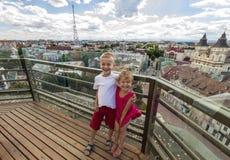 Dos pequeños niños felices sonrientes muchacho y muchacha que se colocan en el top o Fotos de archivo libres de regalías
