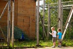 Dos pequeños niños miran un pavo real en un parque zoológico Imagenes de archivo