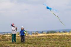 Dos pequeños niños muchacho y muchacha que juegan afuera con una cometa Fotos de archivo libres de regalías