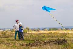 Dos pequeños niños muchacho y muchacha que juegan afuera con una cometa Imágenes de archivo libres de regalías