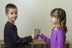 Dos pequeños niños muchacho y muchacha que juegan con el dinero de los dólares Fotografía de archivo libre de regalías