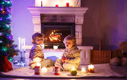 Dos pequeños niños que se sientan por una chimenea en casa en la Navidad Fotografía de archivo libre de regalías