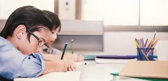 Dos pequeños niños que sientan la mano que sostiene el lápiz y que colorea la imagen Foto de archivo libre de regalías