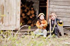 Dos pequeños niños se sientan cerca de una vertiente foto de archivo