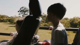 Dos pequeños niños turísticos felices, muchacha y muchacho, gozando excitando paseo en coche del safari en la cámara lenta del bo almacen de video