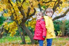Dos pequeños otoños de los muchachos de los mejores amigos y de los niños parquean en cl colorido Fotografía de archivo