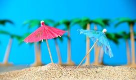 Dos pequeños paraguas en una playa Imagenes de archivo