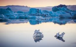 Dos pequeños pedazos de hielo que fluyen y que reflejan en el lago frío con los icebergs grandes detrás, laguna del glaciar del j Foto de archivo libre de regalías