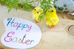 Dos pequeños pollos amarillos y una tarjeta de pascua feliz Foto de archivo libre de regalías