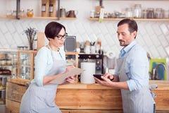 Dos pequeños propietarios de negocio en los delantales que se colocan en café Fotografía de archivo