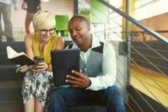 Dos pequeños propietarios de negocio millenial creativos que trabajan en medios estrategia social usando una tableta digital mien Imágenes de archivo libres de regalías