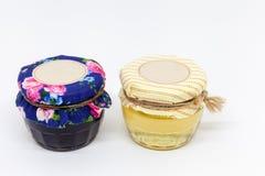 Dos pequeños tarros de cristal de miel y de atasco fotos de archivo libres de regalías