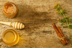 Dos pequeños tarros de miel fresca con el drizzler, canela, flores en fondo de madera Fotos de archivo