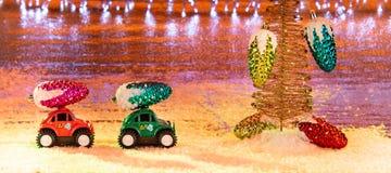 Dos pequeños vehículos todo terreno, transportando decoratio de la Navidad foto de archivo libre de regalías