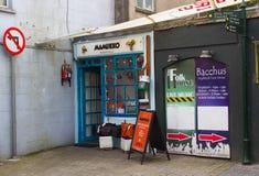 Dos pequeños y premisas poco atractivo de la tienda remetidas en una esquina en las calles traseras de Kinsale en el corcho del c imagen de archivo libre de regalías