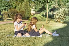 Dos peque?as colegialas que usan smartphone Ni?os que juegan, lectura, mirando el tel?fono imagen de archivo libre de regalías