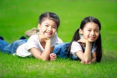 Dos pequeñas muchachas asiáticas que ponen en la hierba Fotografía de archivo