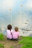 Dos pequeños fishermans en la costa en la lluvia Imagenes de archivo