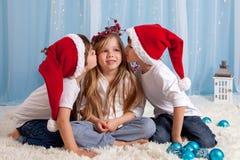 Dos pequeños hermanos gemelos, dando un beso a su hermana, Christm Imágenes de archivo libres de regalías