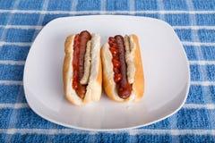 Dos perritos calientes con la mostaza y la salsa de tomate Fotografía de archivo